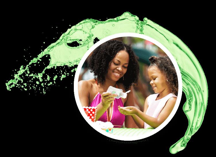 Una madre vertiendo el desinfectante de manos de Glacial en las manos de su hija.
